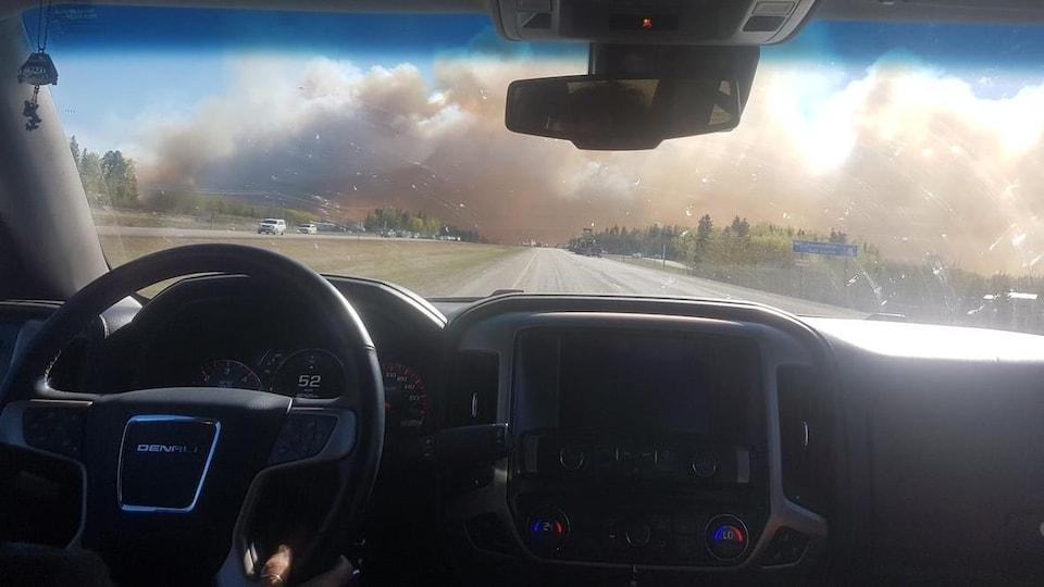 Un automobiliste dans sa voiture regarde la fumée du feu de Marlboro qui l'empêche d'avancer sur l'autoroute 16.