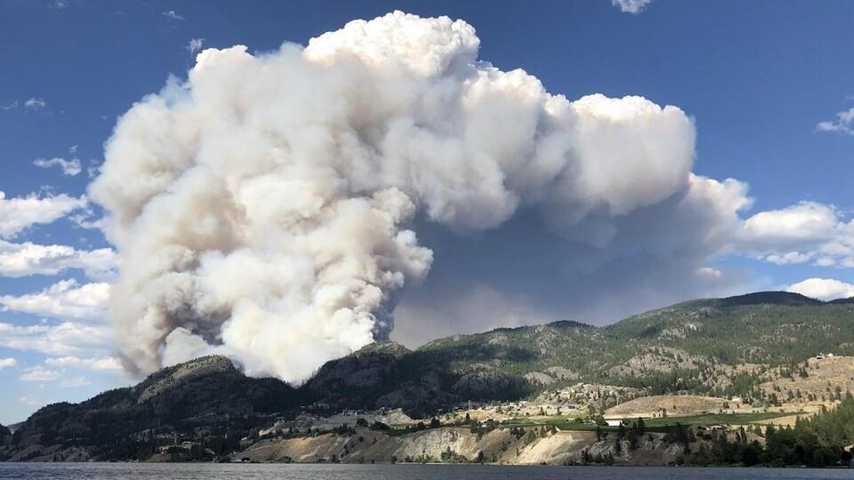 De la fumée s'échappe au-dessus d'une montagne près d'un lac.