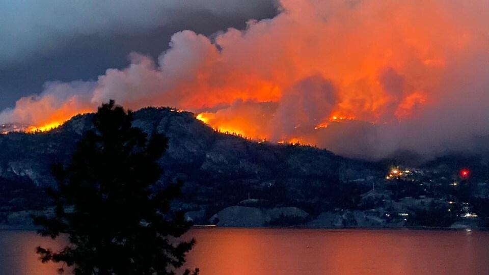 Des flammes et de la fumée s'élèvent au-dessus d'une montagne derrière un lac.