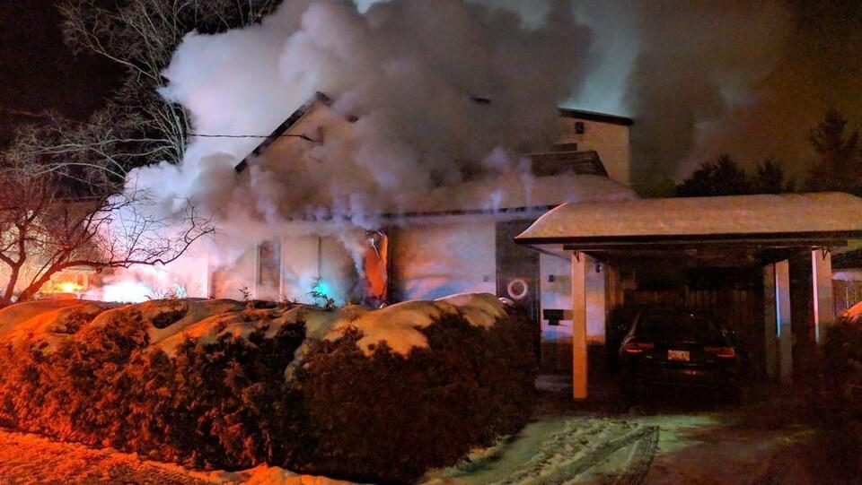 Une maison de laquelle s'échappe beaucoup de fumée lors d'un incendie.