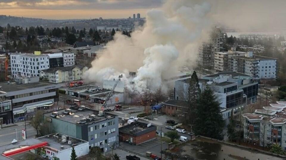 Une importante fumée s'échappant d'un édifice dans un quartier de la ville.