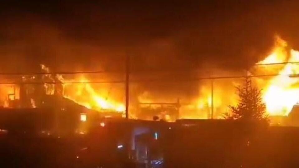 De hautes flammes s'élèvent au-dessus d'un bâtiment qui brûle pendant la nuit.