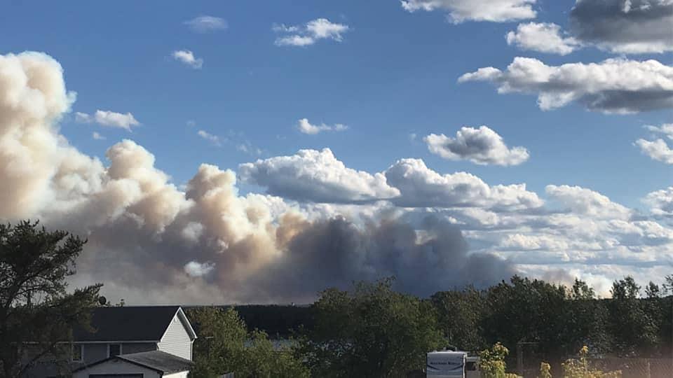 De la fumée derrière le toit d'une maison.