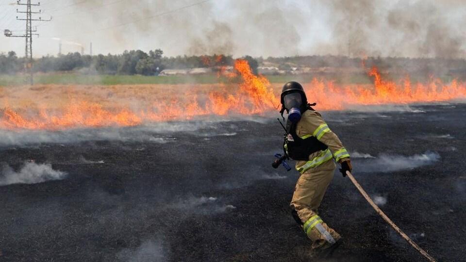 Un pompier traîne un boyau vers un feu qui s'étend à l'horizon.