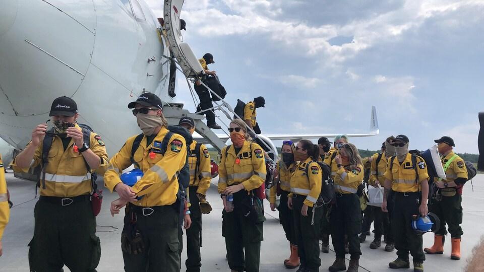 Des pompiers forestiers descendent d'un avion.