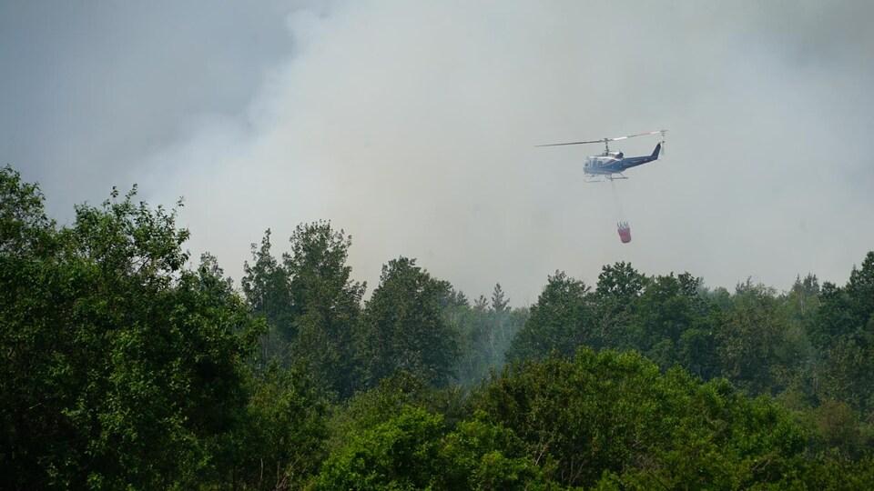 Un hélicoptère s'apprête à déverser de l'eau sur le feu de tourbière à Rivière-Ouelle.