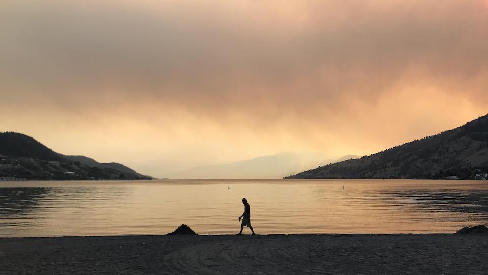 Une personne qui marche sur la plage sous un ciel rouge et brumeux.
