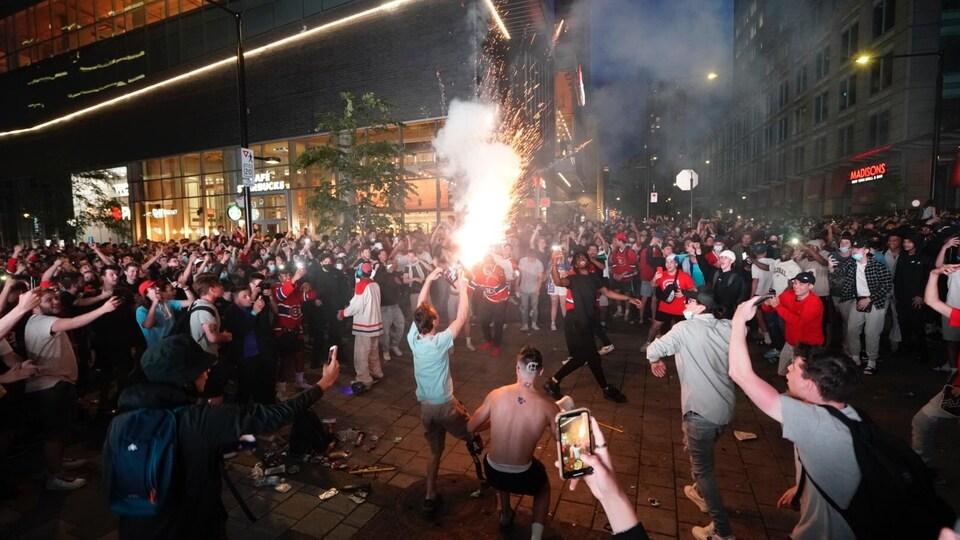 Une foule dispersée autour d'un homme qui tient des feux d'artifice.