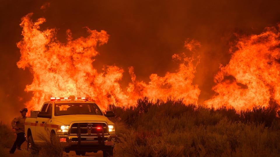 Un pompier court vers son camion alors que le feu avance vers une maison le 17 août 2021 près de Milford, en Californie.