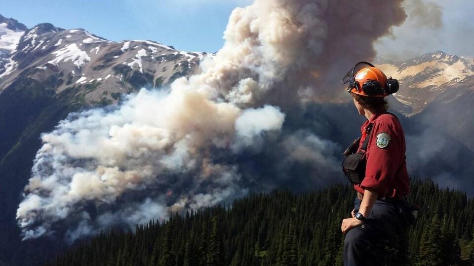 Un pompier sur un flanc de montagne regarde un incendie en train de ravager une forêt.