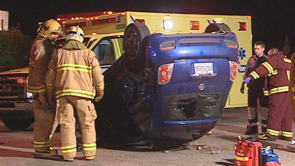 La petite voiture bleue se trouve sur le toit alors que les pompiers et les ambulanciers interviennent sur les lieux