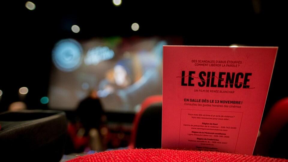 Une feuille sur laquelle est écrit : LE SILENCE, déposée sur un siège dans une salle de cinéma.