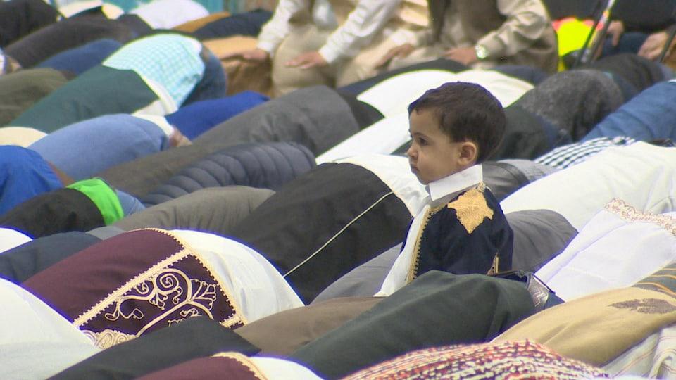 Un enfant parmi des centaines de personnes qui prient.