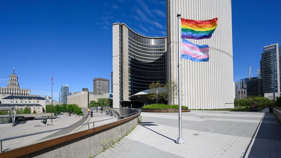 Les drapeaux arc-en-ciel et trans flottent à côté de l'hôtel de ville de Toronto.