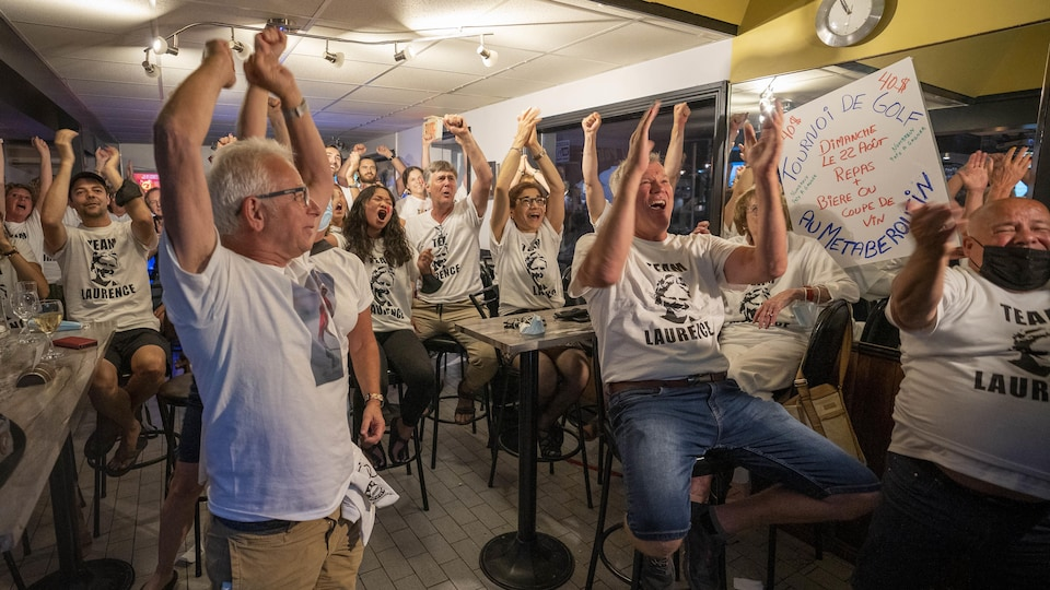 De gens les mains dans les airs, souriants, dans un bar sportif du secteur Cap-de-la-Madeleine.