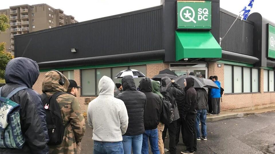 Des personnes font la file devant un point de vente de la SQDC.