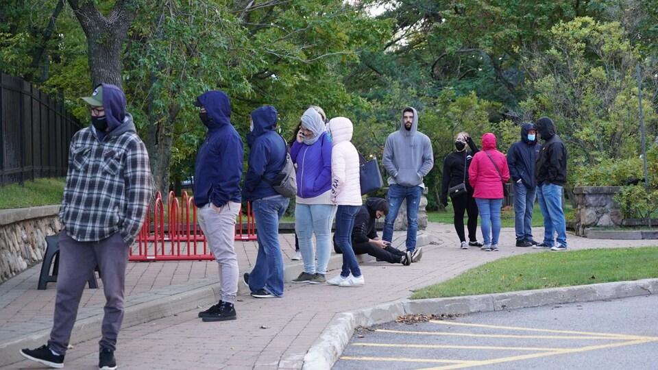 Personnes avec des capuchons qui attendent à l'extérieur.