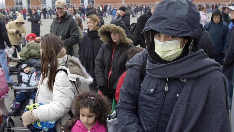 Des personnes font la file à l'extérieur pour recevoir le vaccin contre la grippe H1N1 à l'automne 2009 à Saint-Eustache, au Québec. À l'avant-plan,  on aperçoit une femme portant un masque anti-projections.