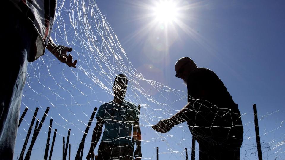 Des pêcheurs réparent un filet maillant à Astoria, en Oregon, en 2012.