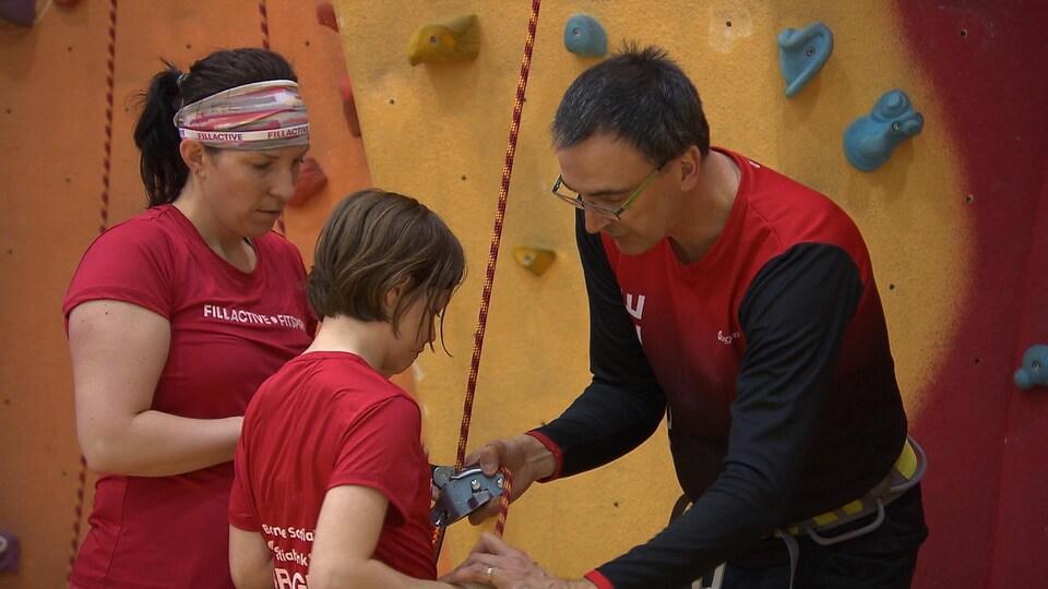 Deux instructeurs aident l'étudiante à installer le harnais.