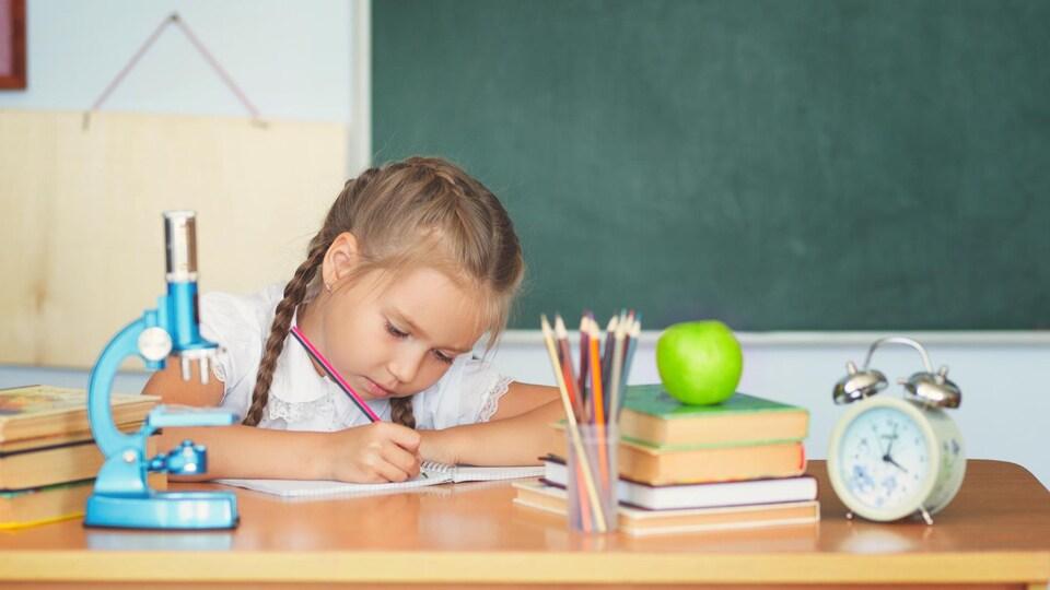Une petite fille fait un dessin, assise à un bureau; devant elle se trouve un microscope.
