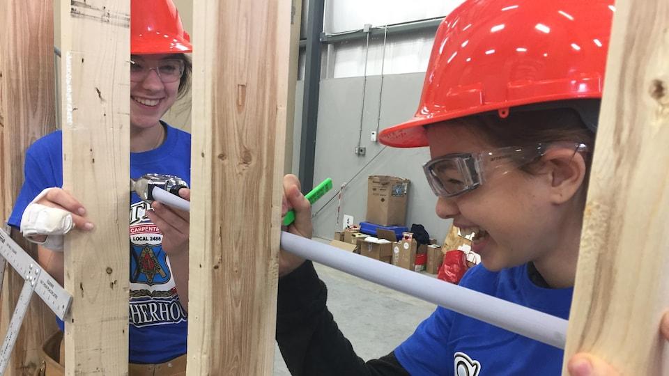 Deux jeunes filles souriantes en équipement de construction tenant un ruban à mesurer, appuyées contre une charpente en bois.