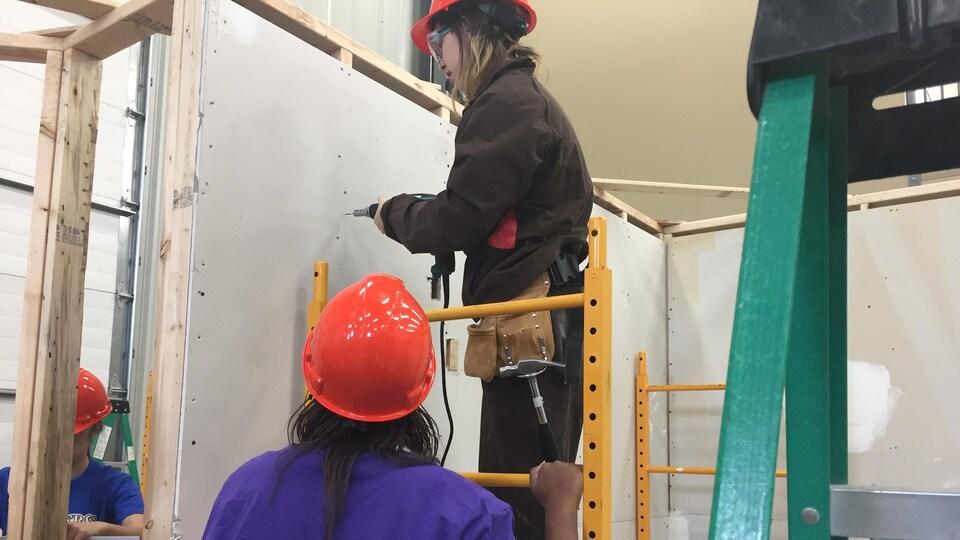 Une jeune fille en habit de construction manipule une perceuse sur un escabot tenu par une autre jeune fille de dos.