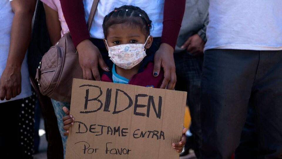 Une fillette portant un masque tient une pancarte en carton.