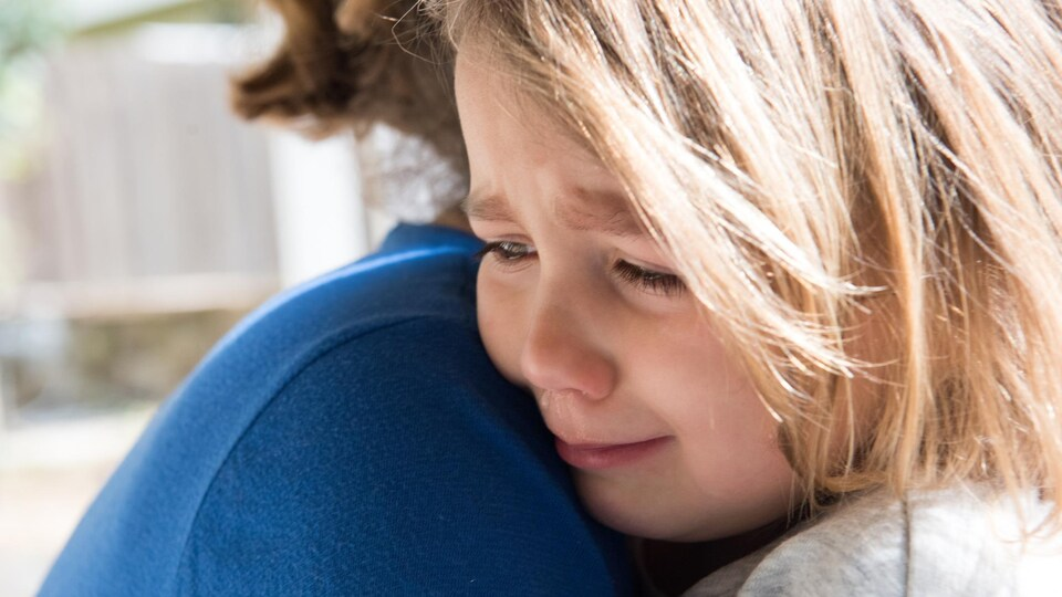 Une femme prend dans ses bras une fillette triste.