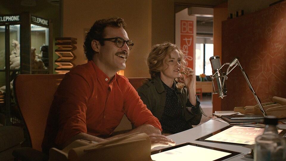 Les deux acteurs devant un micro et des écrans
