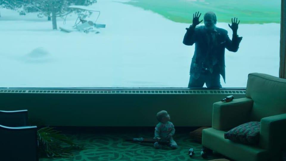 Un zombie regarde un bébé à travers la vitre d'une grande salle.