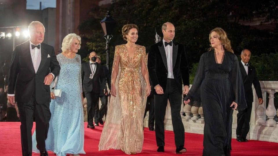 Three women wearing long dresses and two men are on the red carpet.