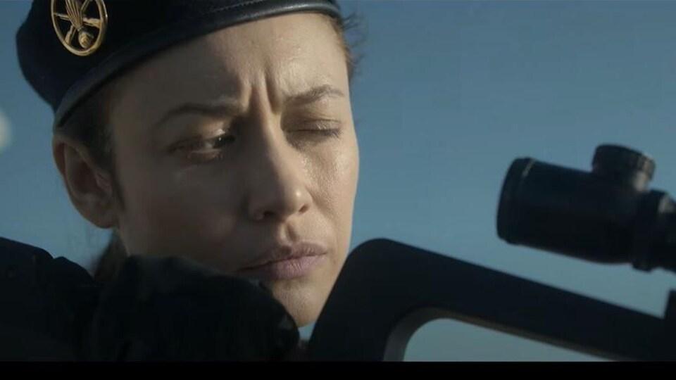Une soldate regarde dans la lunette d'un fusil.