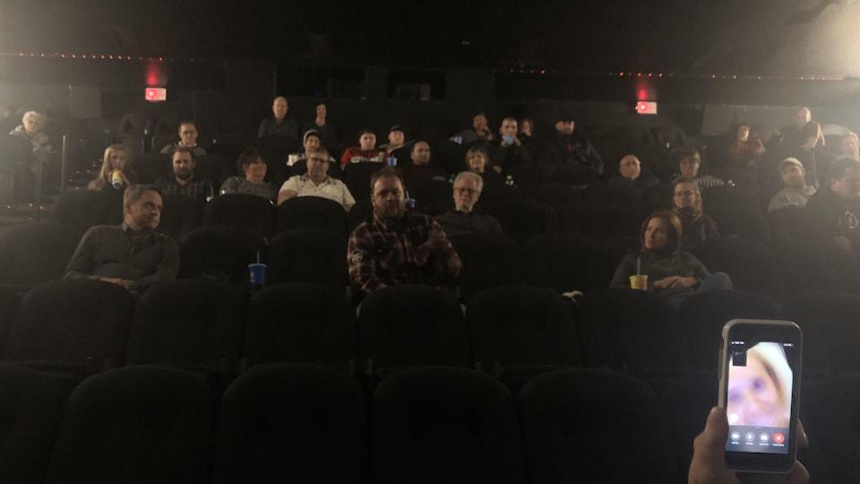 Plusieurs personnes sont assises dans la salle de cinéma. Certaines avec deux bancs entre elles. Sophie Dupuis parle en vidéoconférence.