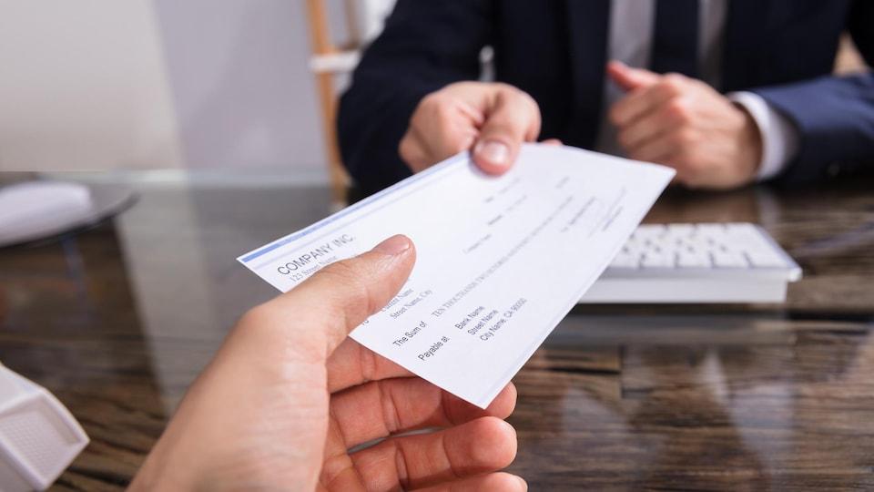Une personne remet un chèque à une autre personne
