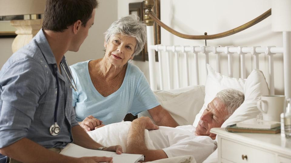 Un médecin au chevet d'un homme couché dans son lit, à la maison.