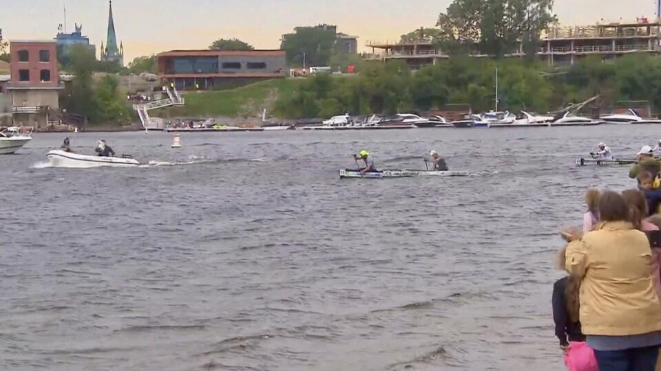 Des canotiers sur la rivière Saint-Maurice, à Trois-Rivières, devant quelques spectateurs.