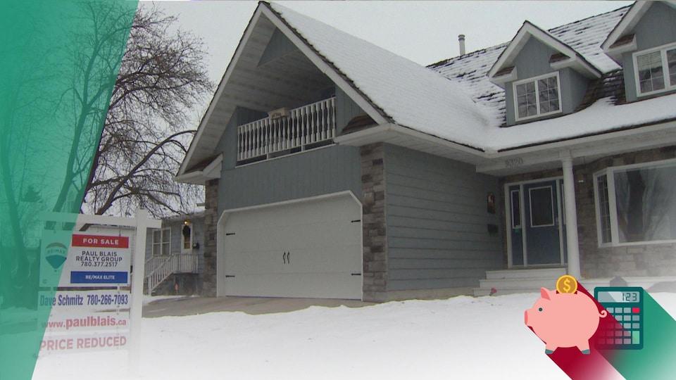 Une maison grise recouverte de neige. Devant la maison, une pancarte qui indique que son prix a été réduit.
