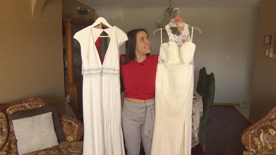 Une jeune fille tient deux robes à bout de bras.