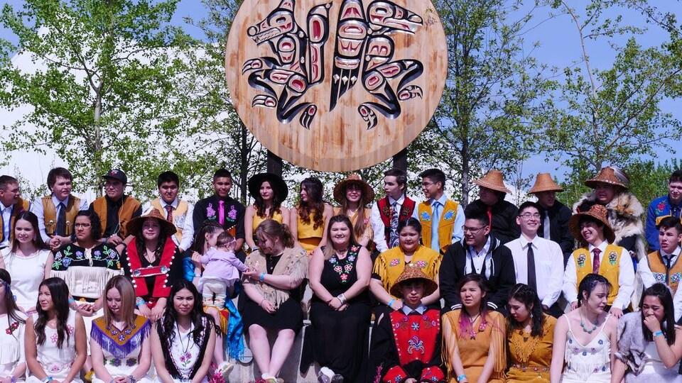 Les finissants à Whitehorse sont assis en trois rangées avec derrière eux une grande sculpture ronde autochtone.
