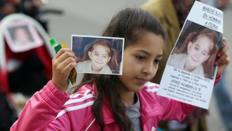 e77931f9fe7 Une fillette tient dans ses mains des affiches montrant le visage de la  petite Fiona lors