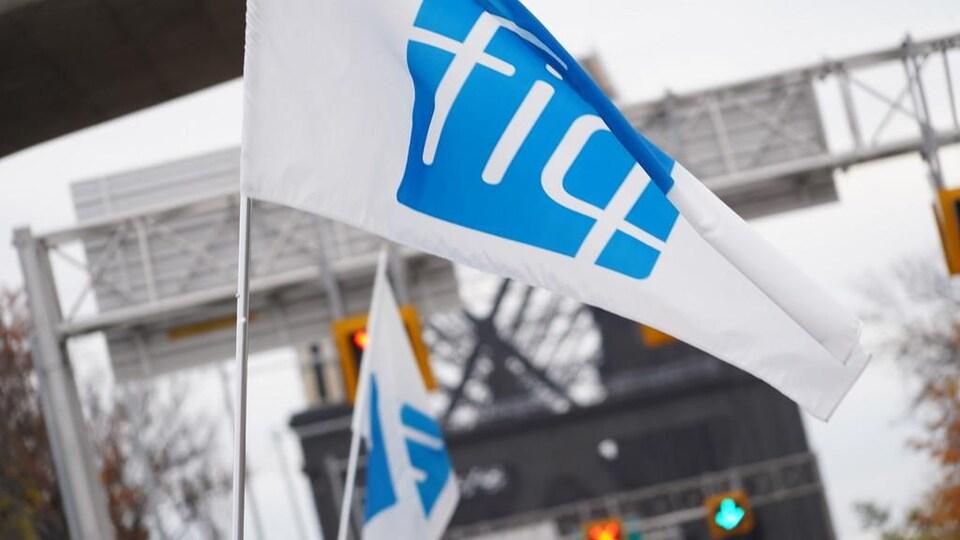 Un drapeau de la FIQ brandi devant le pont de Québec.