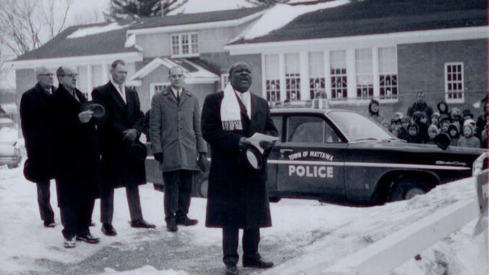 Photo en noir et blanc de plusieurs hommes à coté du voiture de police