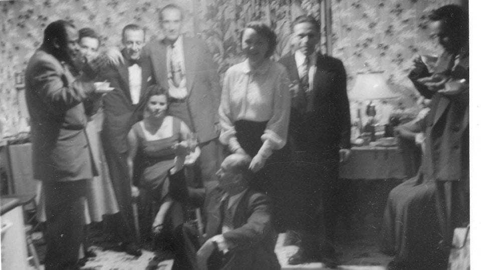 Photo en noir et blanc, plusieurs personnes réunies dans la salle à manger d'un logement.