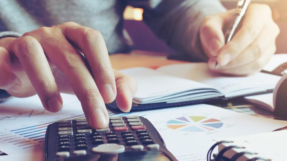 Gros plan sur un homme utilisant une calculatrice.