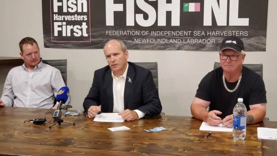 Les trois hommes assis à une table donnent une conférence de presse