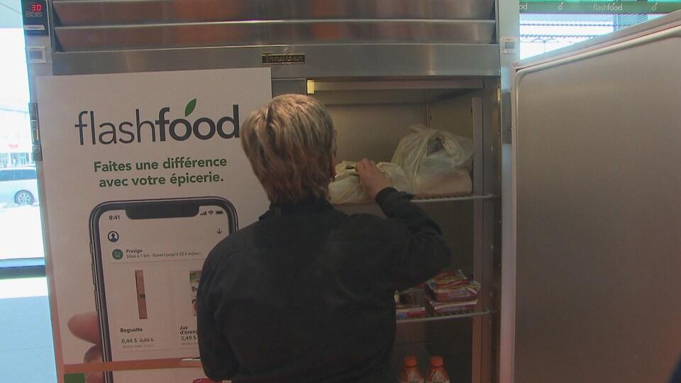Une commis dépose un sac dans le réfrigérateur Flashfood.