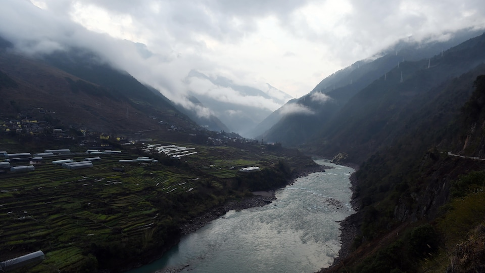 Un cours d'eau s'étire à l'horizon, entre les montagnes. Des nuages très bas rendent le paysage brumeux et gris. Sur les rives se trouvent des rizières.