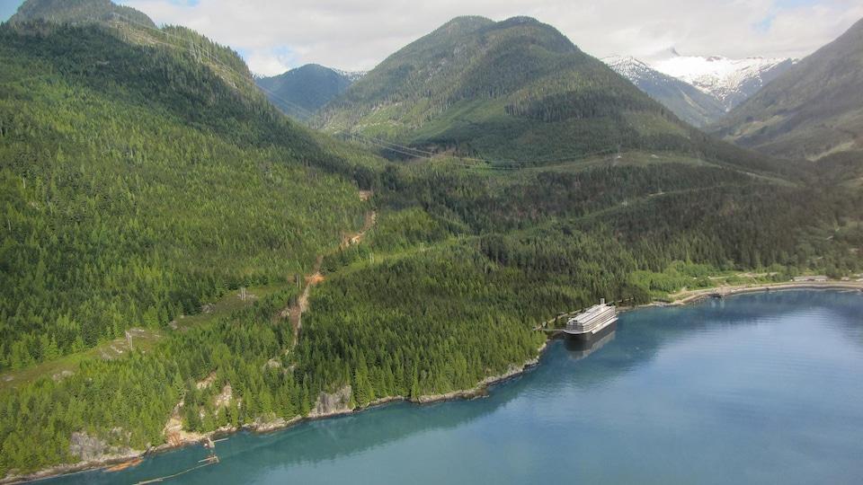 Image d'une barge insérée dans une photo de la baie Howe, où l'on voit la baie entourée de montagnes.