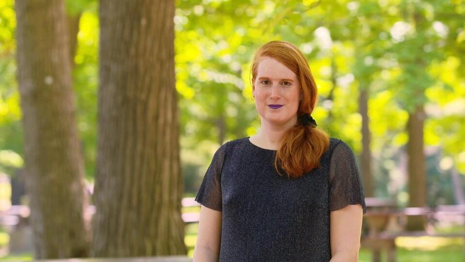 Une femme sourit à la caméra au milieu d'un parc.